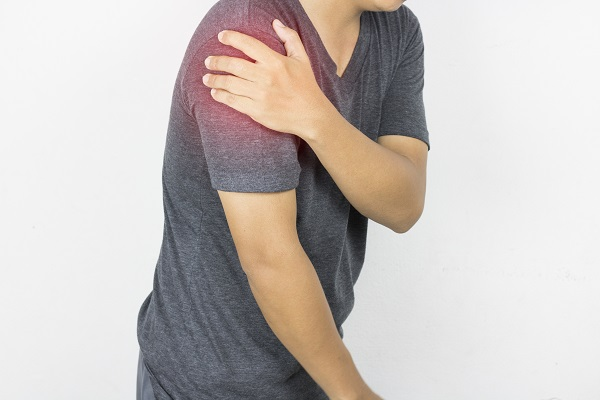 Man in gray t-shirt is shoulder ache, concept as health care and medicine
